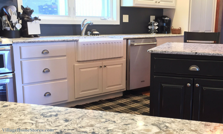 Farmhouse sink in white kitchen with black island. | VillageHomeStores.com