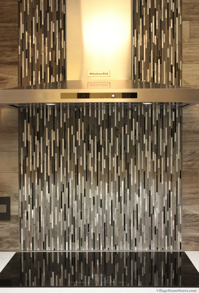 A Glazzio mosaic tile cascades down behind a stainless steel hood. | VillageHomeStores.com