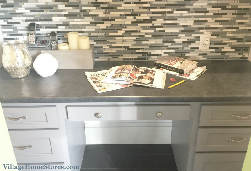Gray painted cabinetry and glass mosaic tile backsplash in a Home Office. | VillageHomeStores.com