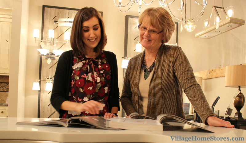 Lighting experts Keri Swanberg and Mary Beth Farber review catalogs in the new Village Home Stores lighting showroom. | VillageHomeStores.com