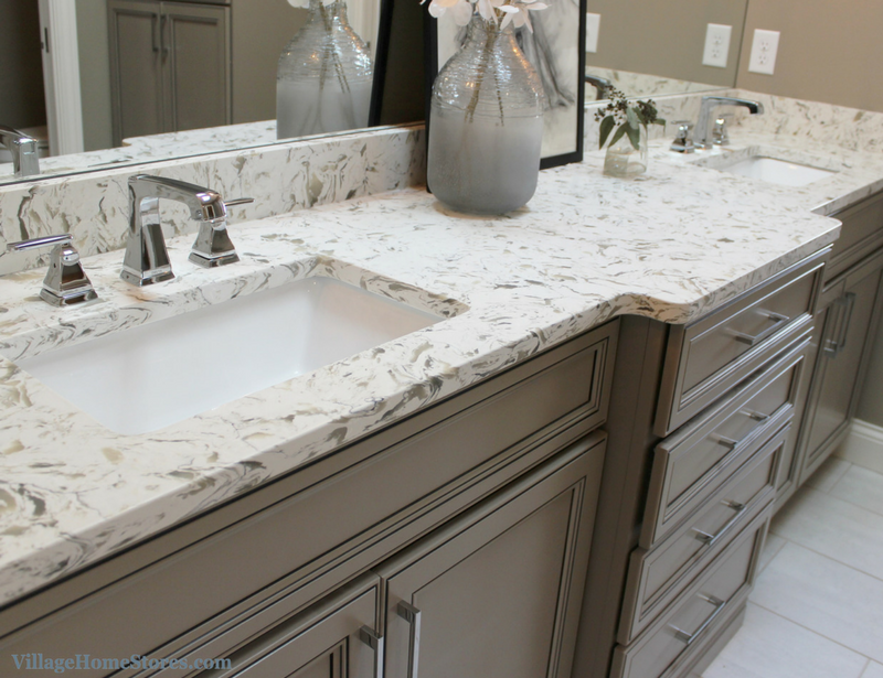 Gray painted master bath cabinetry from Koch paired with quartz tops. Design by Village Home Stores for Heartland Builders. | VillageHomeStores.com