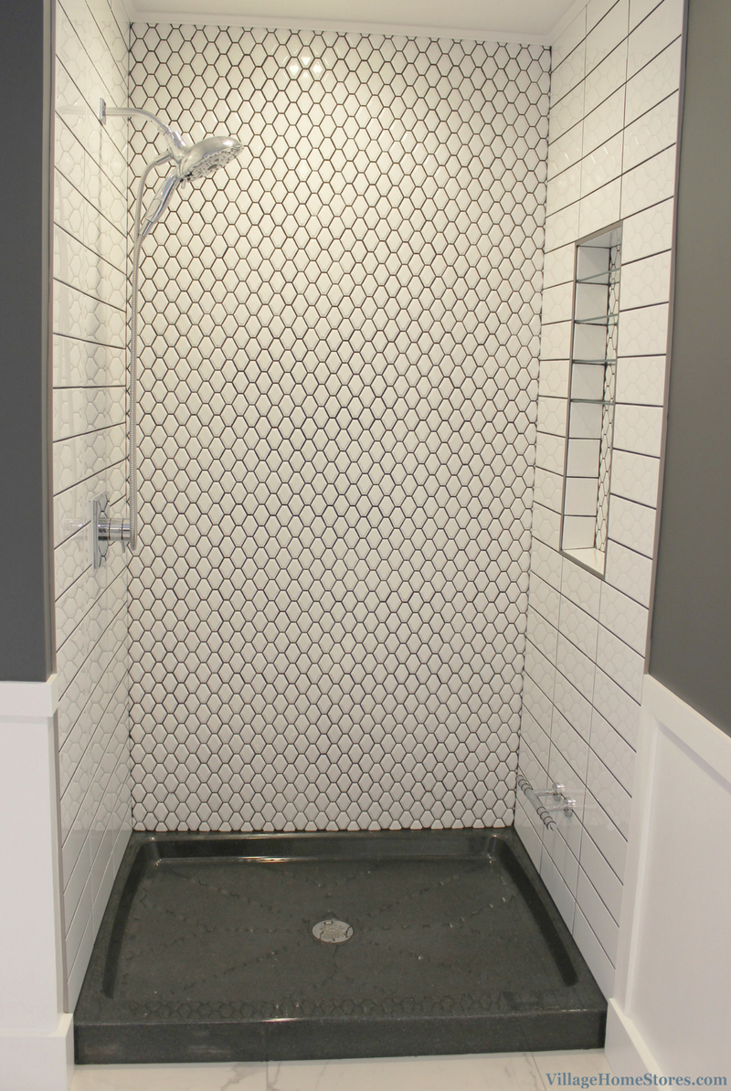 Remodeled Quad Cities bathroom with custom tiled shower including modern shapes and a dark gray grout. | VillageHomeStores.com