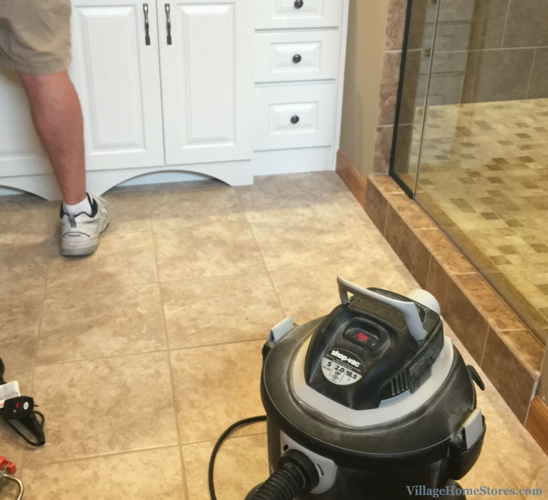 Bathroom remodeling team from Village Home Stores cleaning up the finished project. | VillageHomeStores.com