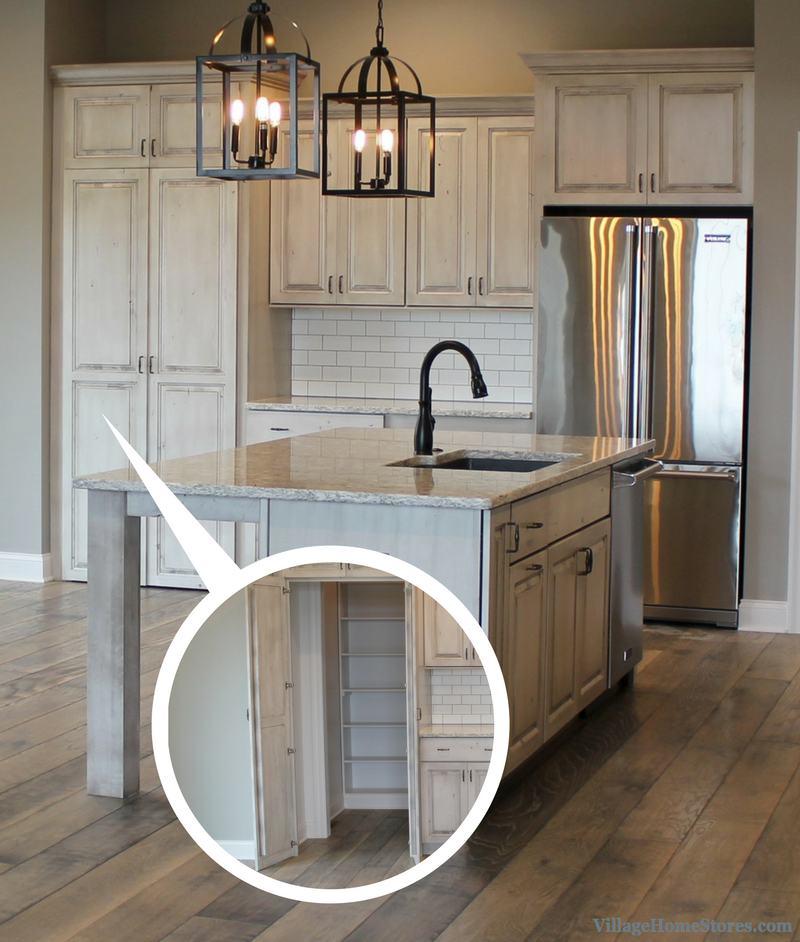 White Drift painted kitchen with hidden pantry front. Kitchen design by Village Home Stores. | VillageHomeStores.com