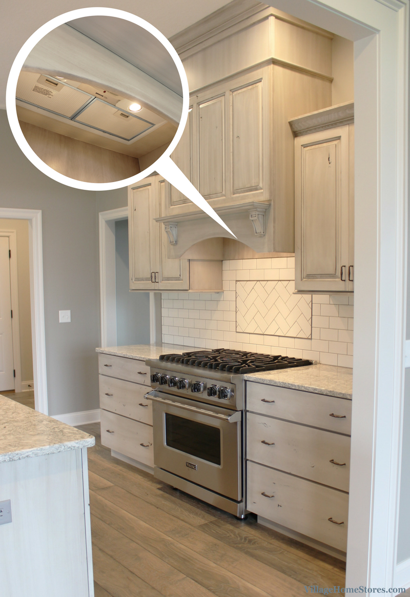 White Drift painted kitchen with wood hood and Broan insert. Kitchen design by Village Home Stores. | VillageHomeStores.com