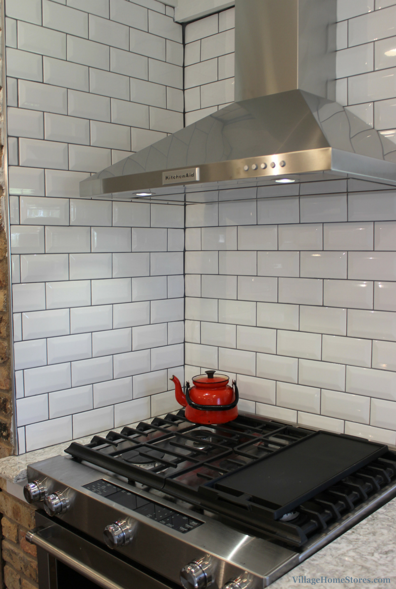 A Prophetstown, IL kitchen with beveled subway tile and chimney hood. | VillageHomeStores.com