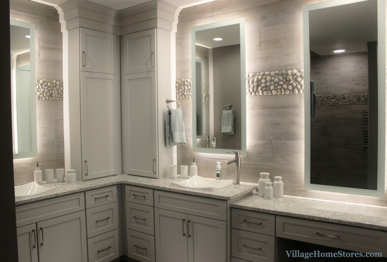 DuraSupreme cabinetry and custom backlit mirrors on tiled wall. Remodeled Davenport bathroom by Village Home Stores. | VillageHomeStores.com