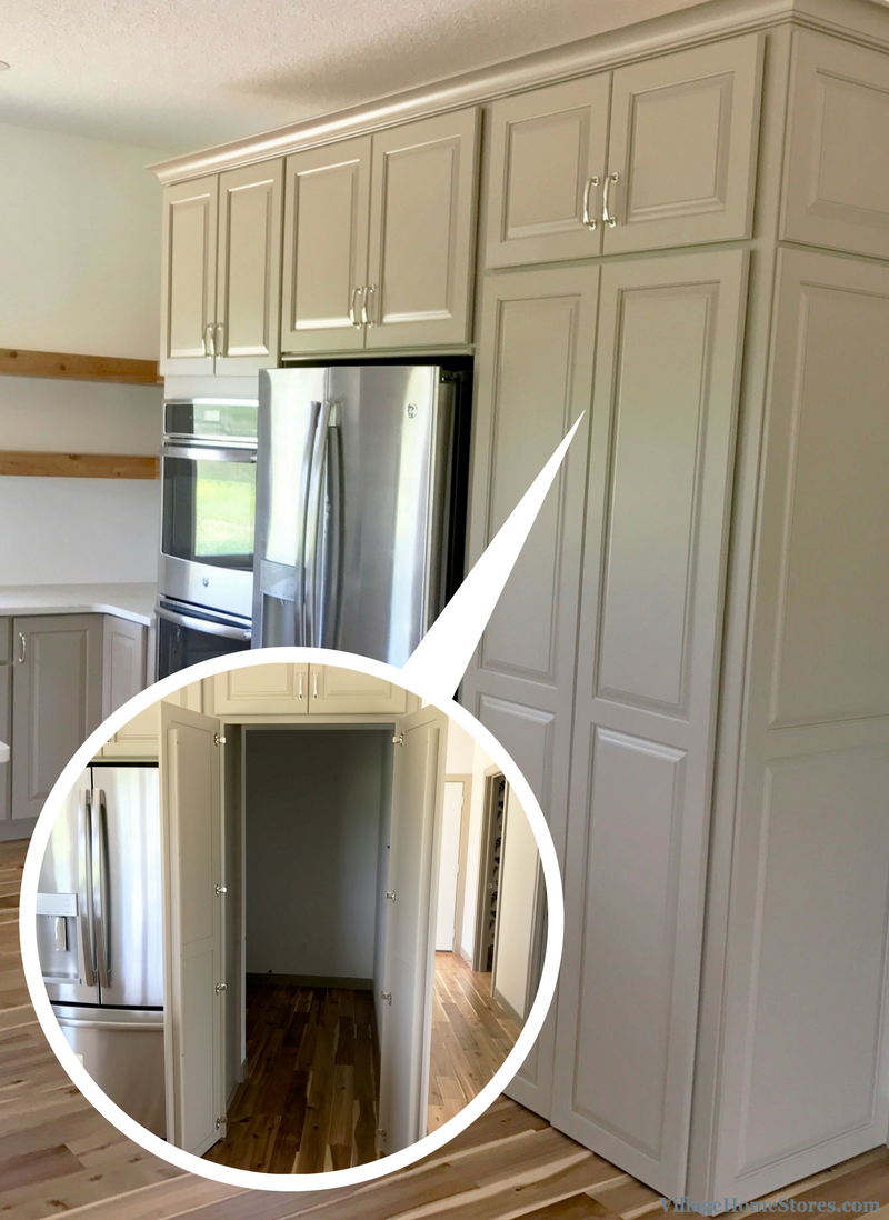 A walkin pantry front in an Andalusia, IL kitchen with painted Taupe cabinets and Carrara Grigio quartz tops. | VillageHomeStores.com