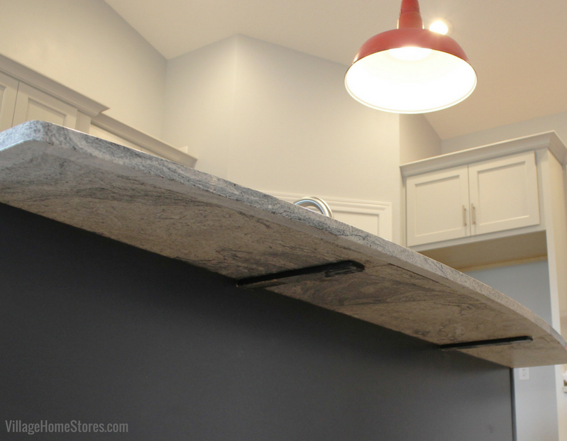 Granite support brackets installed beneath an island counter overhang. Design and materials by Village Home Stores for Hazelwood Homes. | VillageHomeStores.com