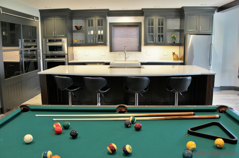 A lower level kitchen installed in a recreation room featuring DuraSupreme cabinetry and Cambria Quartz tops. | VillageHomeStores.com