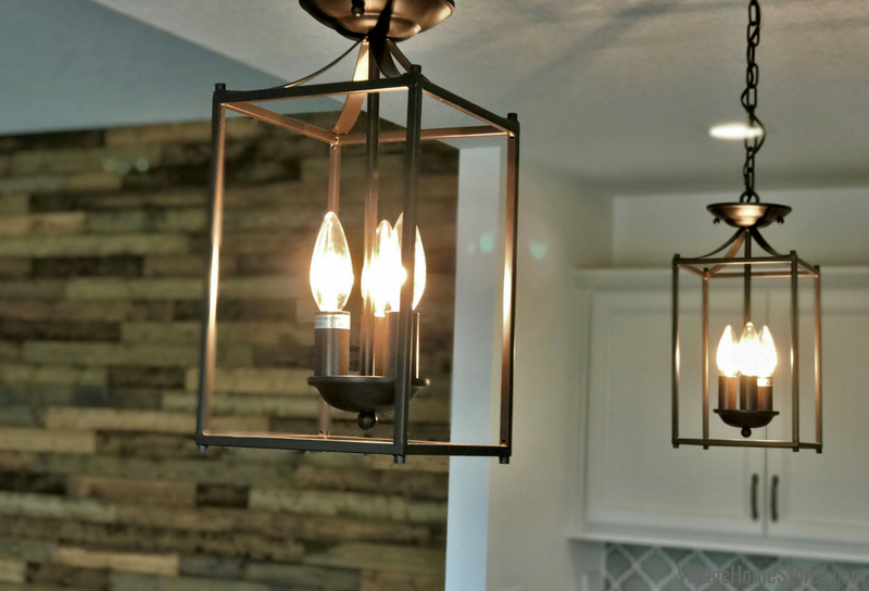 Lantern style lights above a kitchen island. Colona Illinois New Home by Hazelwood Homes with design and materials from Village Home Stores. | villagehomestores.com