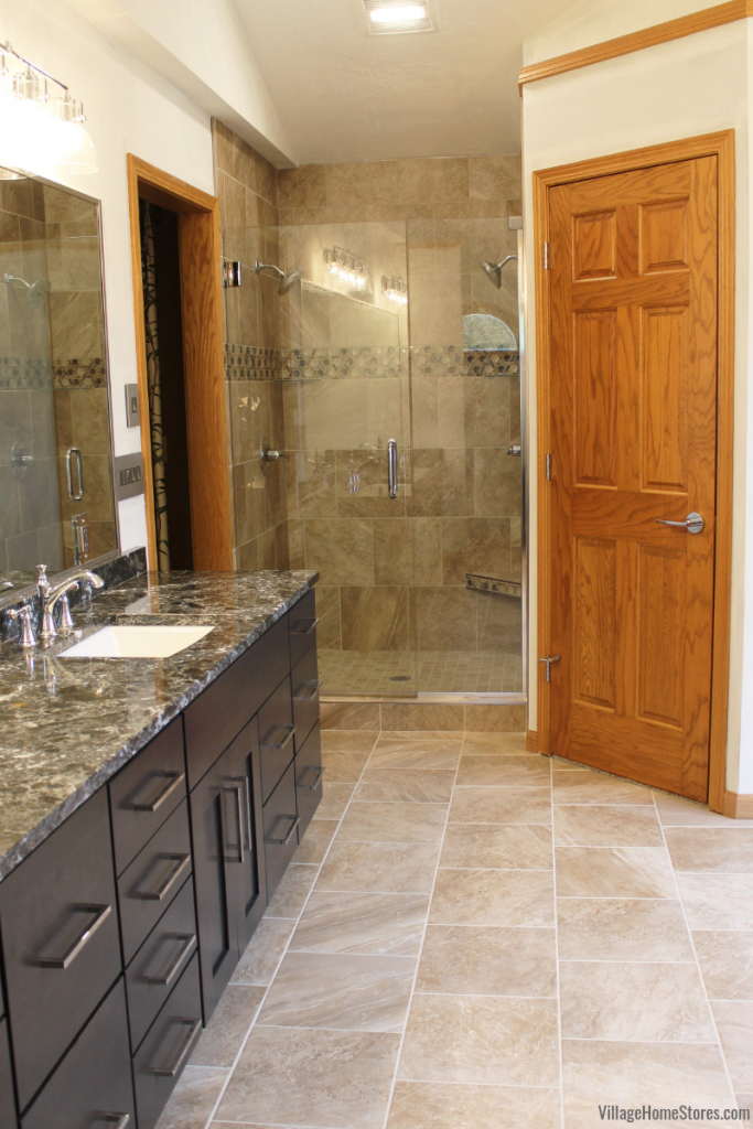 Custom tiled shower and a double bowl vanity in a Moline, IL bathroom remodeled from start to finish by Village Home Stores. | villagehomestores.com