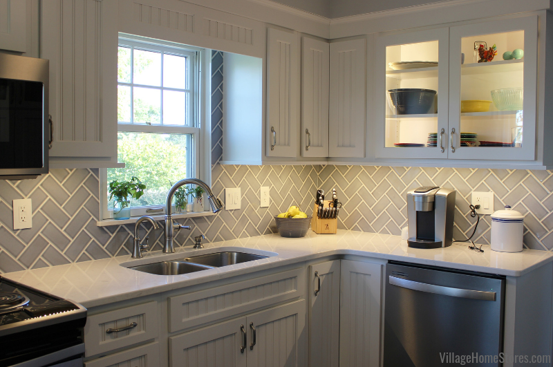Koch cabinetry, Cambria Swanbridge quartz, and blue subway tile backsplash in a Geneseo kitchen. Complete remodel from start to finish by Village Home Stores. | villagehomestores.com