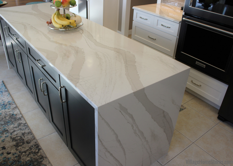 Two tone kitchen in Bettendorf, Iowa with Cambria Brittanicca Warm quartz counters installed with a waterfall design on the island. Kitchen designed and remodeled from start to finish by Village Home Stores. | villagehomestores.com