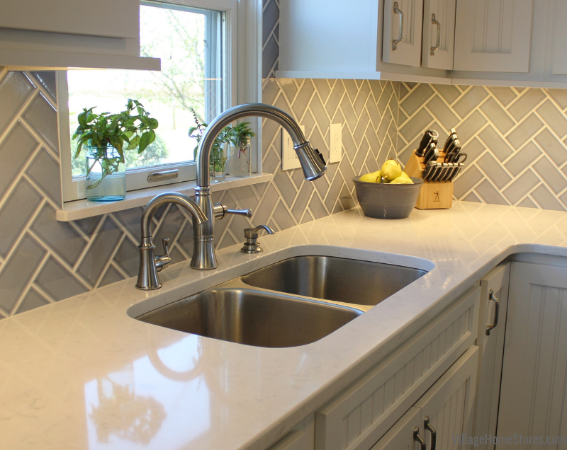 Cambria Swanbridge quartz counters and a gray-blue subway tile in a Geneseo farmhouse kitchen. Complete kitchen remodel from start to finish by Village Home Stores. | villagehomestores.com