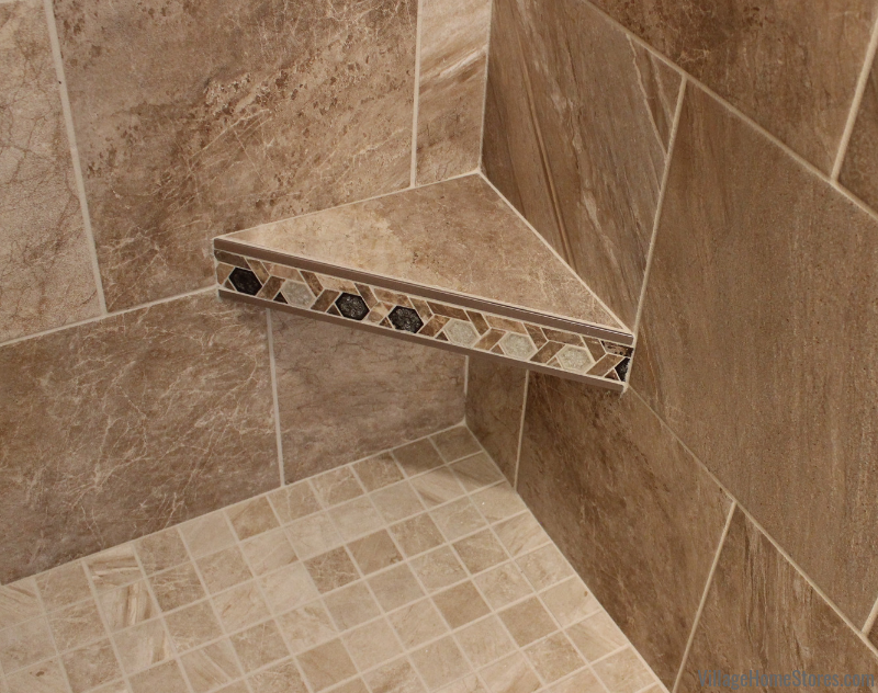 Tiled shower with a corner footrest shelf in a Moline, IL bathroom remodeled from start to finish by Village Home Stores. | villaehomestores.com