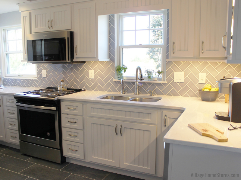 Koch cabinetry, Cambria Swanbridge quartz, blue subway tile, and Whirlpool appliances in a Geneseo farmhouse. | VillageHomeStores.com