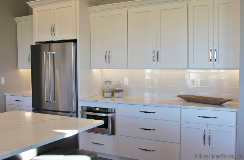 Bettendorf, Iowa kitchen with white painted cabinets, a gray stained island, KitchenAid appliances, and quartz tops. | villagehomestores.com
