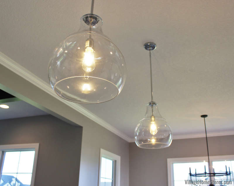 Glass pendant lighting hangs above a kitchen island in a Bettendorf, Iowa home. Kitchen design and materials by Village Home Stores for Kerkhoff Homes in the Quad Cities. | villagehomestores.com