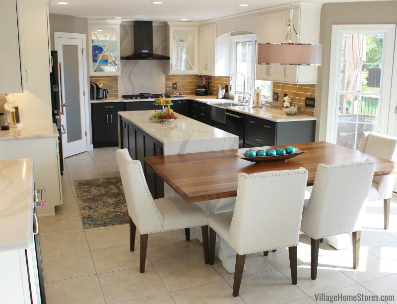 Two tone kitchen in Bettendorf, Iowa with large kitchen island, waterfall Cambria counters, Black Stainless appliances, and a custom walnut wood top table. | villagehomestores.com