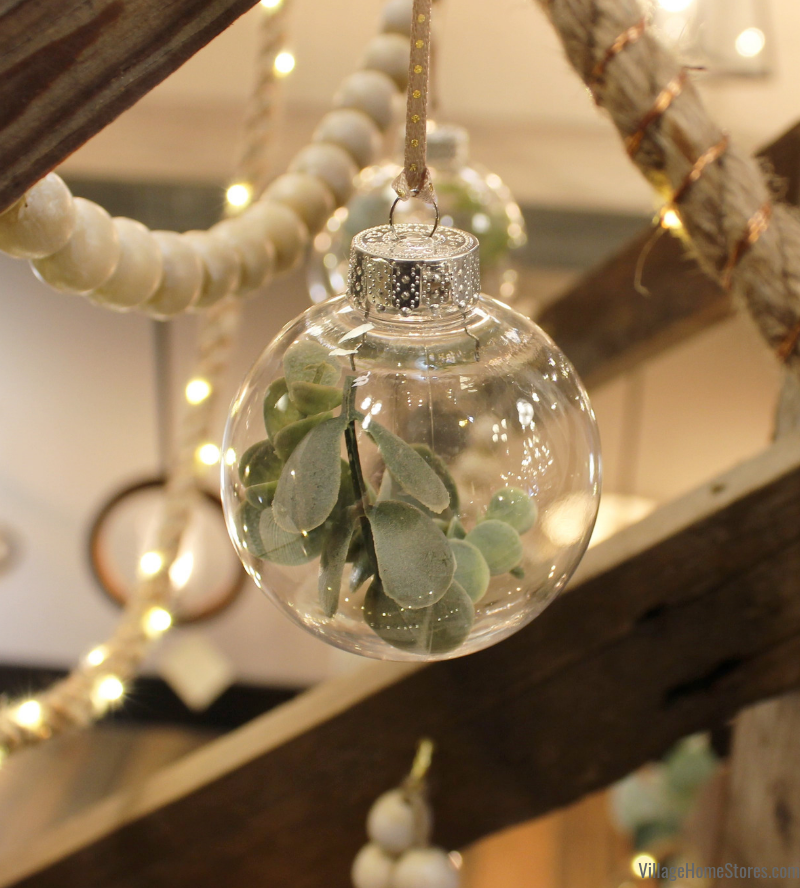 Great eucalyptus ornament DIY idea! Take clear ornaments and fill with faux greenery. | villagehomestores.com