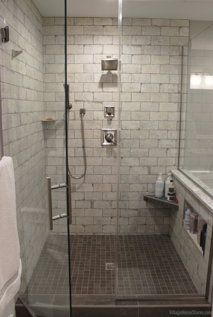 Custom tiled shower with glass door installed in a remodeled Bettendorf Iowa bathroom. Bathroom remodel from start to finish by Village Home Stores. | villagehomestores.com