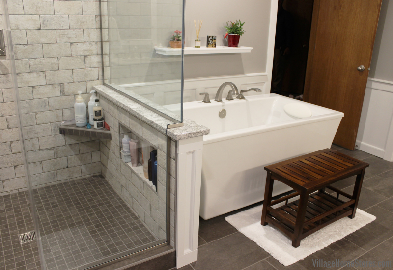 Custom tiled shower and freestanding bathtub in a remodeled Bettendorf Iowa bathroom. Bathroom remodel from start to finish by Village Home Stores. | villagehomestores.com