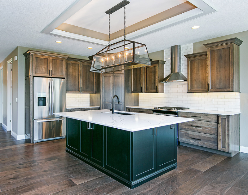 Tailored Rustic Transitional Hickory kitchen with gray Stone stain and painted black island. Kitchen cabinetry and lighting by Village Home Stores for Advance Homes of the Quad Cities. | villagehomestores.com