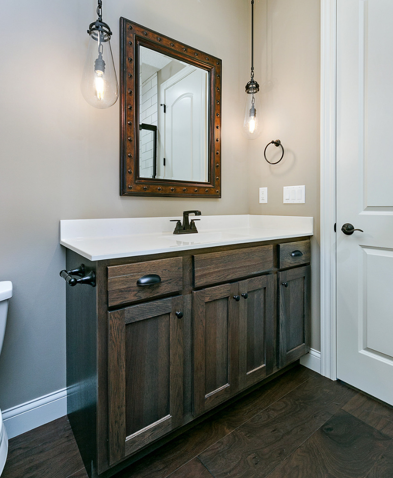 Gray stained bathroom cabinetry and ELK Gramercy pendant lights. Cabinetry and lighting by Village Home Stores for Advance Homes of the Quad Cities. | villagehomestores.com