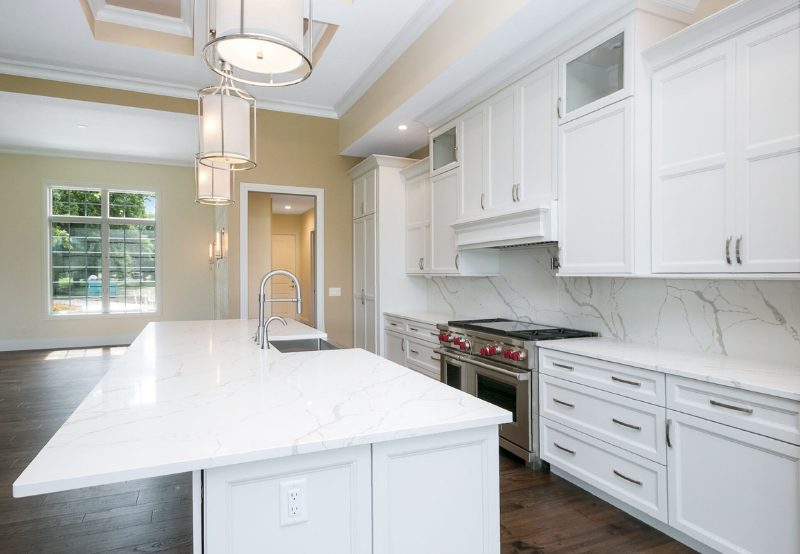 Custom Amish White painted kitchen cabinetry and Quartz with large island design by Village Home Stores. Photo and home by Heartland Builders of the Quad Cities.