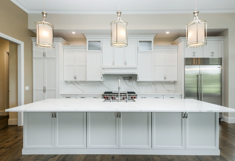 Custom Amish White painted kitchen cabinetry and Quartz with full height backsplash by Village Home Stores. Photo and home by Heartland Builders of the Quad Cities.