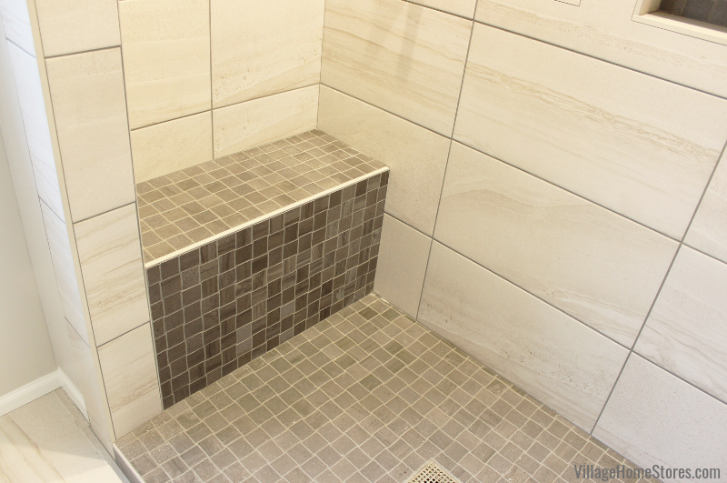 Custom tiled shower with bench in an Eldridge, Iowa master bathroom remodeled start to finish by Village Home Stores. | villagehomestores.com
