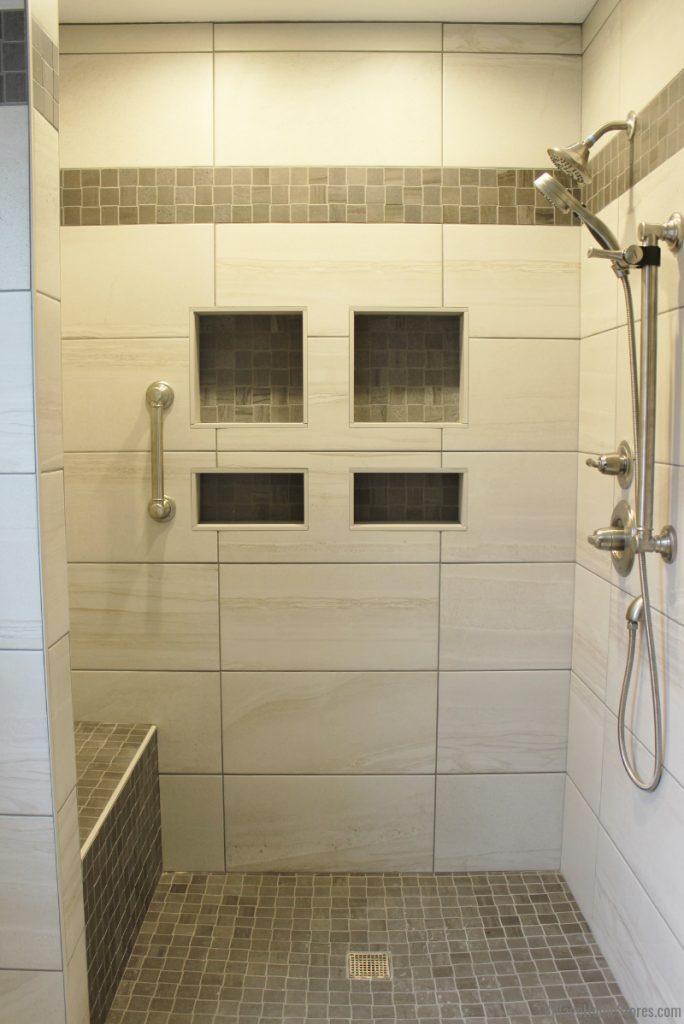 Custom tiled shower with wall niches in an Eldridge, Iowa master bathroom remodeled start to finish by Village Home Stores. | villagehomestores.com