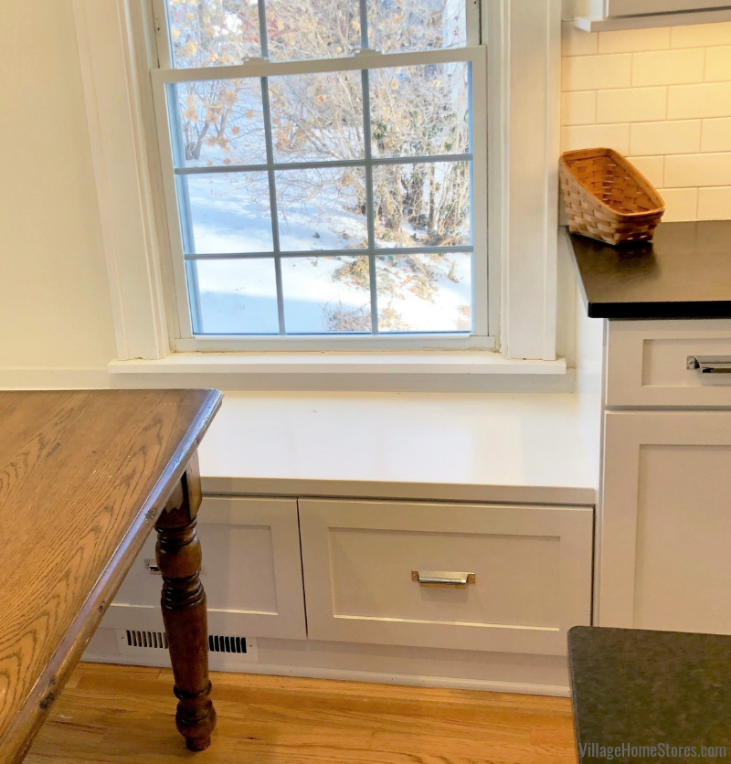 White painted kitchen with built in bench seat in historic McClellan Heights district of Davenport, IA remodeled from start to finish by Village Home Stores. | villagehomestores.com