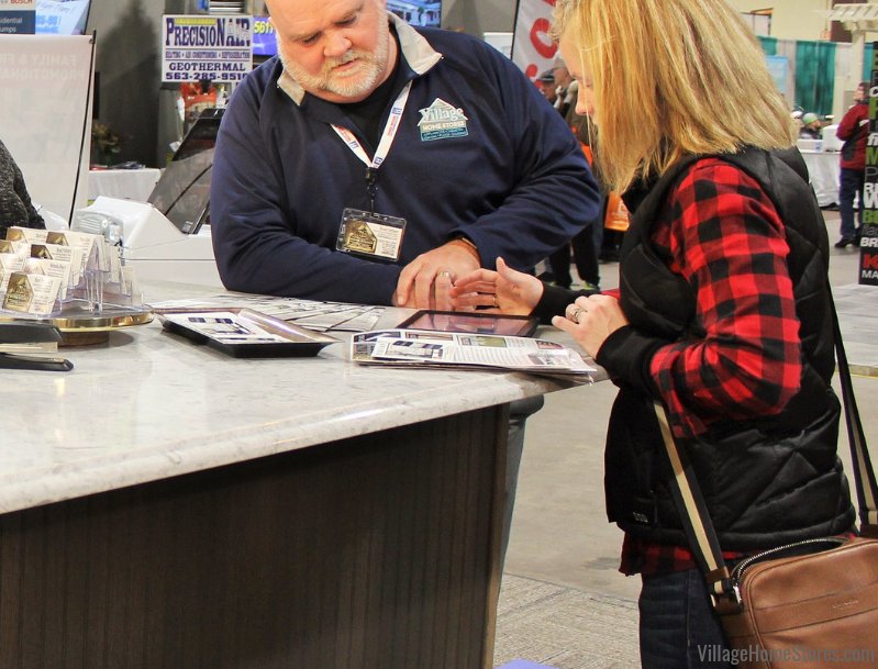 A Quad Cities area customer chats about her project with a member of the Village team at the QCBR Home Show. | villagehomestores.com