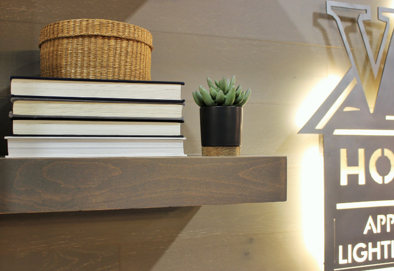 Stick on wall planks and floating gray shelves designed and installed by Village Home Stores. | villagehomestores.com