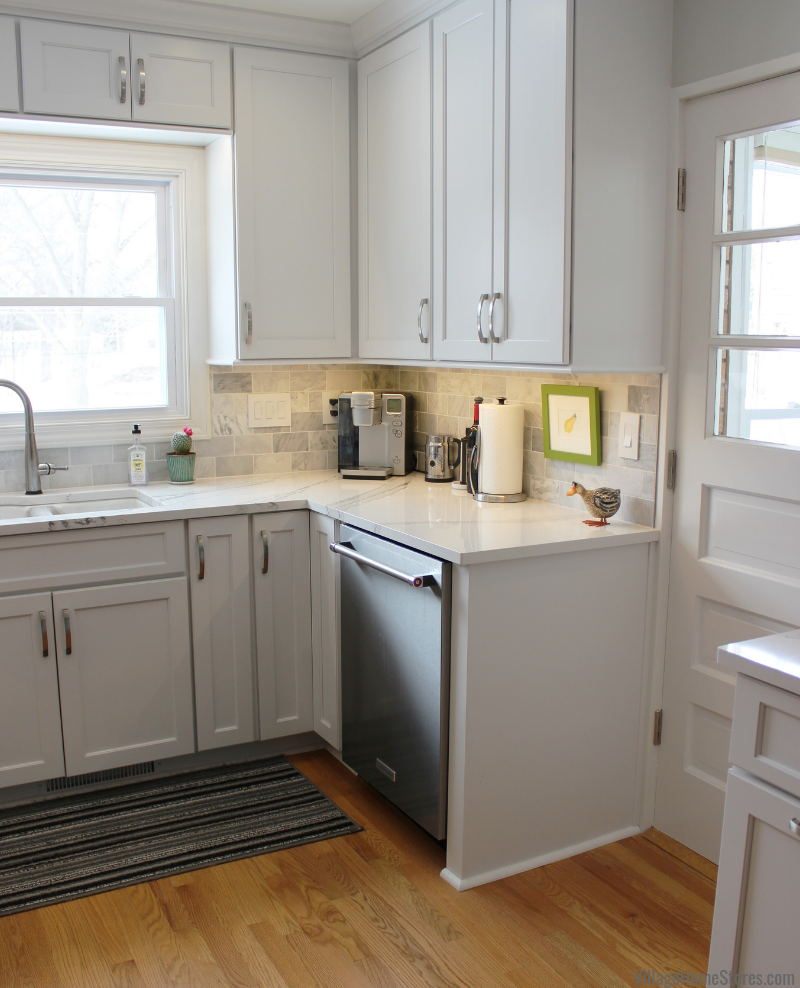 White painted kitchen with marble look quartz counters and stainless KitchenAid appliances in Moline, IL. Complete remodel from start to finish by Village Home Stores. | villagehomestores.com