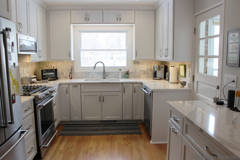 White painted kitchen with marble look quartz counters in Moline, IL. Design, material selection, and complete remodel from start to finish by Village Home Stores. | villagehomestores.com