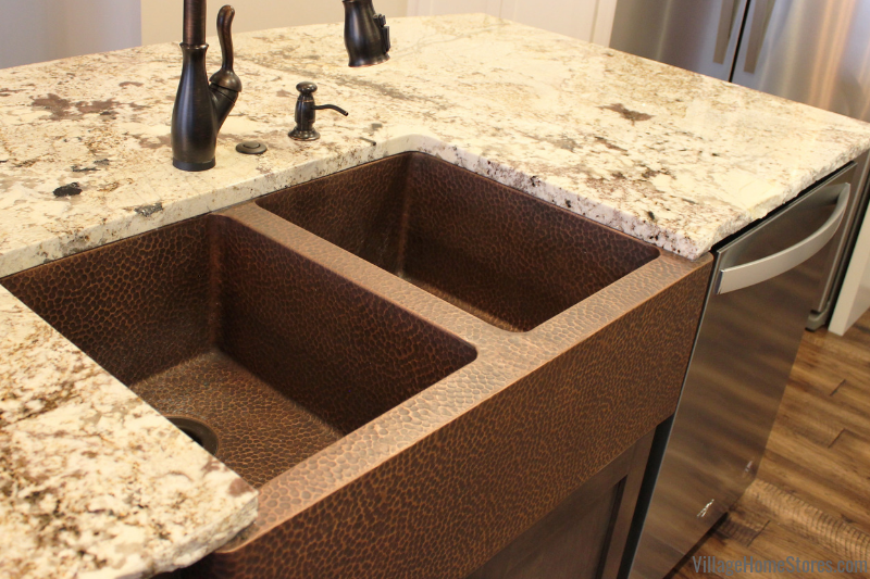 Copper farmsink from LeNova installed in Desert Beach granite counters with a chiseled edge profile. Kitchen design and materials by Village Home Stores for Hazelwood Homes.