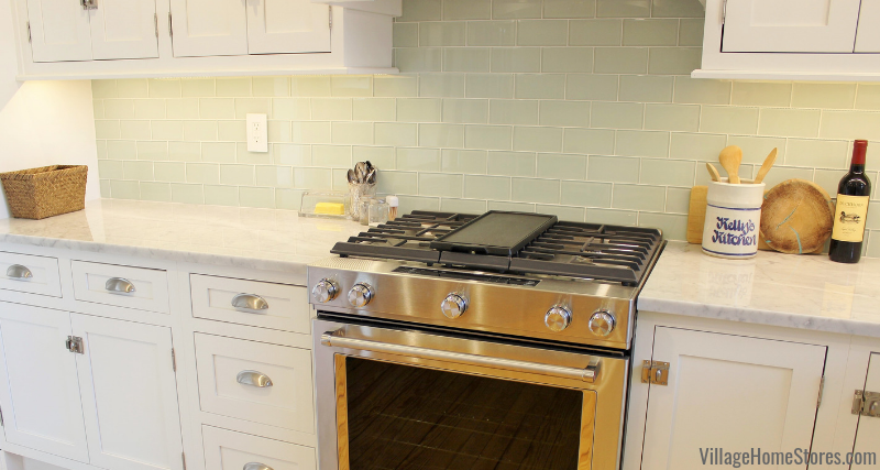 White remodeled kitchen with glass subway tile and Stainless Steel KitchenAid gas range. Complete kitchen remodel from start to finish by Village Home Stores.