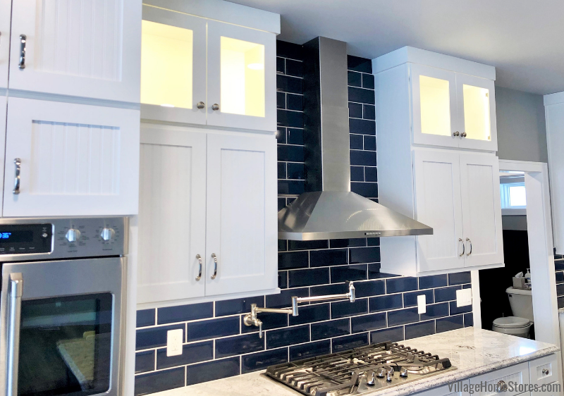 Beveled blue Azura wall tiles and White Dura Supreme cabinetry in a Prophetstown, IL kitchen. Design and materials from Village Home Stores for Hazelwood Homes of the Quad Cities.