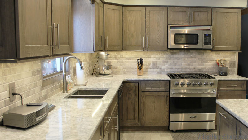Limestone gray kitchen wall tile paired with Dura Supreme Cabinetry in Red Oak wood and gray stain. Cambria Berwyn Quartz counters and Viking appliances also featured. Kitchen designed and remodeled from start to finish by Village Home Stores.