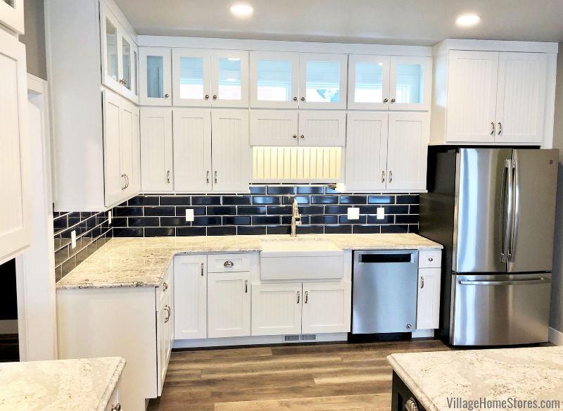 Backless glass-front cabinets in Prophetstown, IL paired with blue wall tile and Cambria quartz countertops from Village Home Stores for Hazelwood Homes of the Quad Cities.