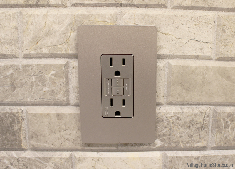 Colona kitchen with our radiant series of switches and outlets. Installed with gray limestone wall tiles. Kitchen lighting and tile by Village Home Stores.