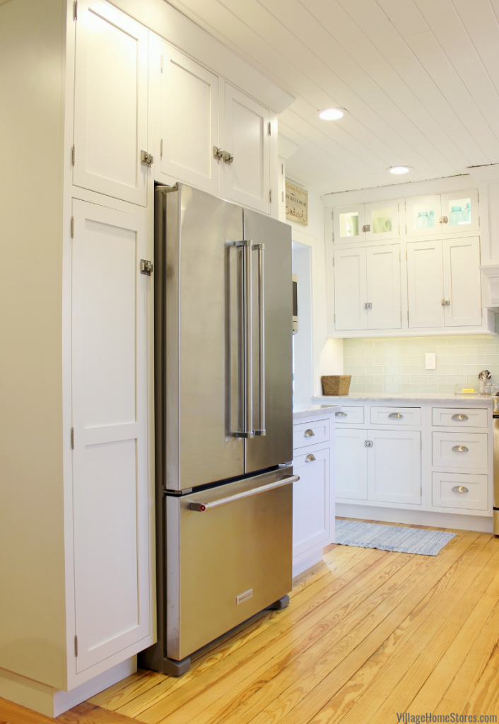 White inset kitchen with farm sink, Stainless Steel appliances, and ship lap ceiling treatment. Kitchen design and complete remodel from start to finish by Village Home Stores.