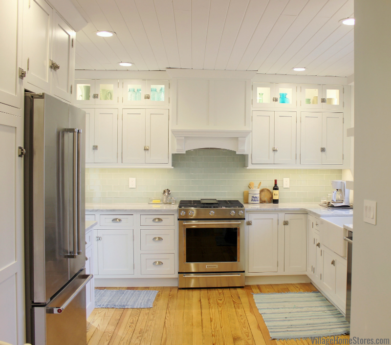 White inset kitchen with farm sink, wood hood, Stainless Steel appliances, and ship lap ceiling treatment. Kitchen design and complete remodel from start to finish by Village Home Stores.