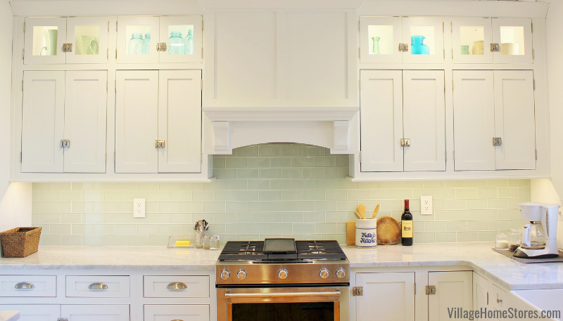 White remodeled kitchen with glass subway tile backsplash and custom wood range hood. Complete kitchen remodel from start to finish by Village Home Stores.