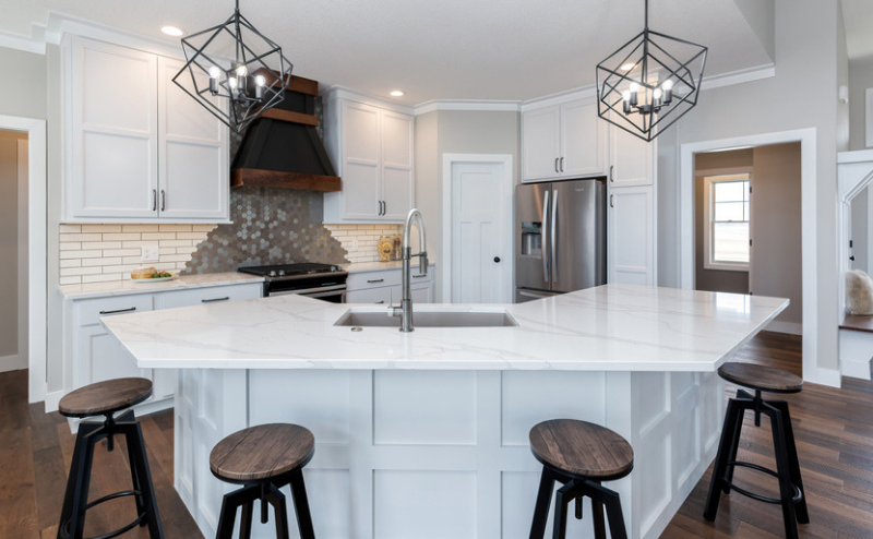 Unique white painted kitchen with angled island in Bettendorf, Iowa. QCBR Parade of Homes stop Spring 2019 McCoy Homes, Quad Cities.