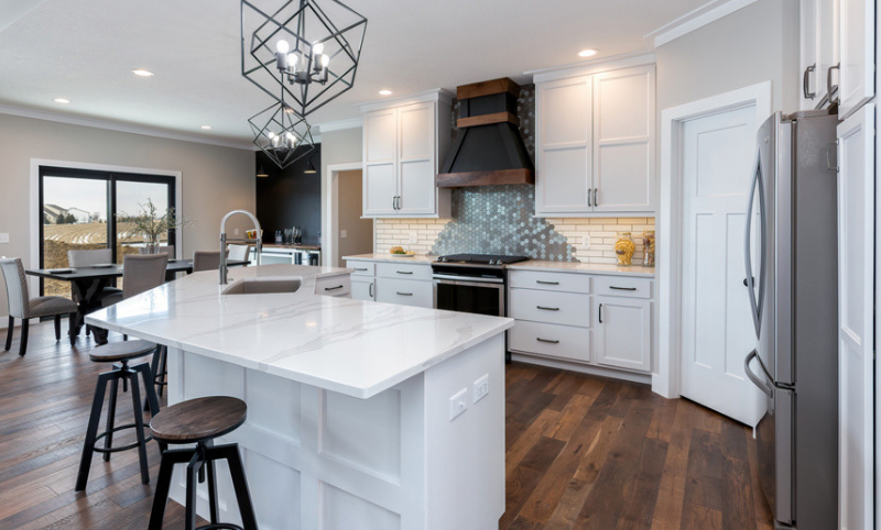 White painted kitchen with angled island, marble-look quartz counters, and Whirlpool appliances from Village Home Stores.