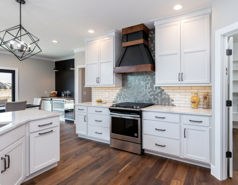 White painted kitchen with marble-look quartz counters and Whirlpool appliances from Village Home Stores.